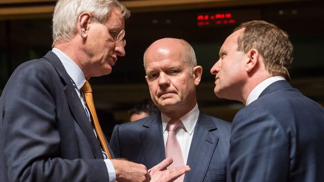 Drei Männer diskutieren miteinander.