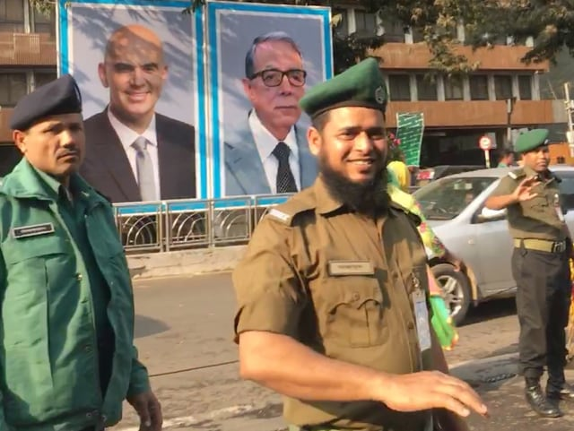 Sicherheitsleute sichern die Strassen in Dhaka. Auch an dieser Strasse ist ein grosses Plakat mit dem Foto von Alain Berset angebracht. (srf)