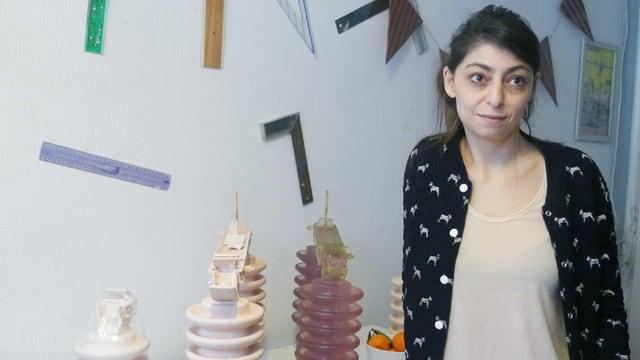 Eine junge Künstlerin steht neben ihren Skulpturen.