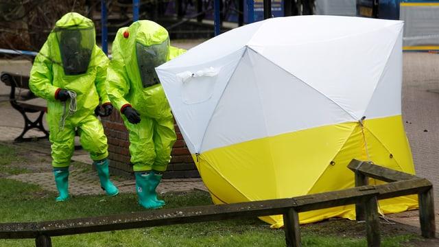 Zwei Polizisten in gelben Schutzanzügen nähern sich einem weiss-gelben Zelt.