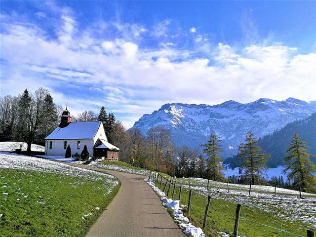 Ein Weg führt zur Kappelle, auf den Wiesen liegt wenig Schnee, im Hintergrund verschneite Berge
