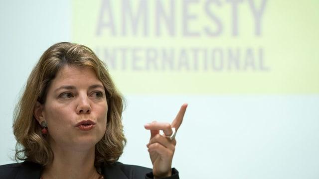 Blonde Frau redet vor Amnesty Schriftzug