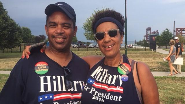 Eine Afroamerikanerin mit ihrem Arm um einen Afroamerikaner. Beide tragen Hillary Clinton for President T-Shirts.