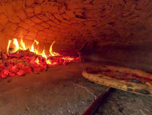 Pizza wird eine einem Pizzaofen gebacken.