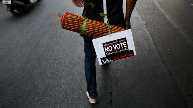 Regierungsgegner mit einem Fleyer zum Wahlboykott.
