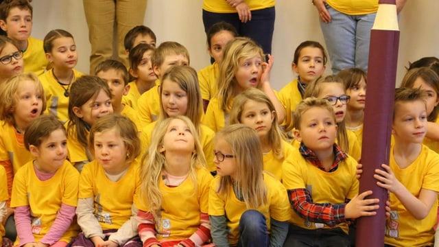 scolaras e scolars che portan tuts in t-shirt mellen