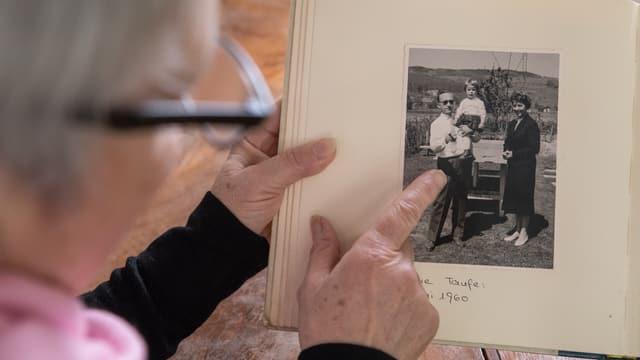 Eine Frau zeigt auf ein offenes Fotoalbum. Zu sehen ist eine Schwarz-Weiss-Aufnahme eines kleinen Kindes auf dem Arm eines Mannes. Daneben steht eine Frau.