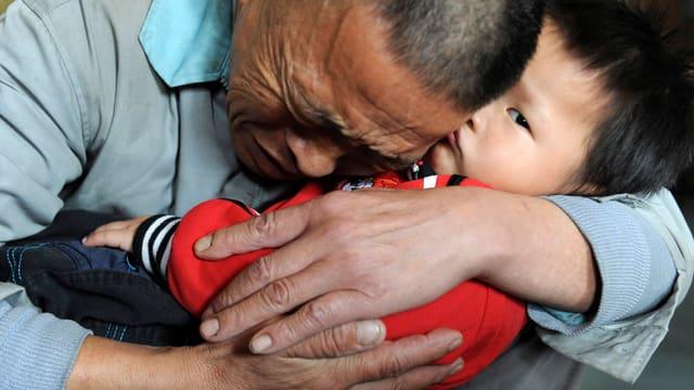 Ein Vater umarmt seinen Sohn in China.