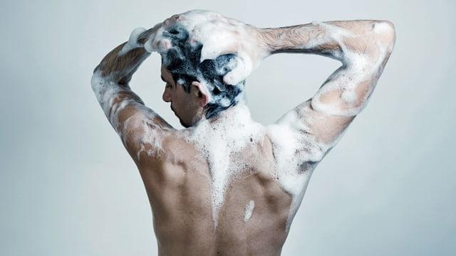 Mann in der Dusche seift sich ein.