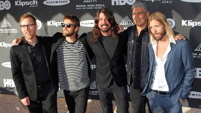 Foo Fighters Gruppenfoto vor Fotowand.