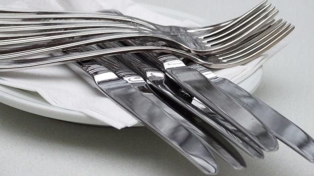 Sauberes Besteck auf einem Teller.