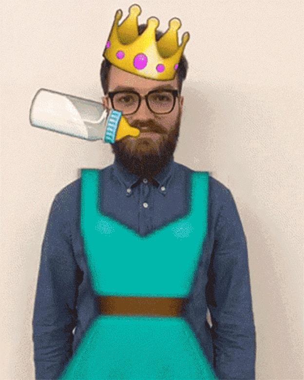 Einem jungen Bartträger wird eine Emoji-Krone aufgesetzt, ein Emoji-Damenkleid angezogen und eine Emoji-Babyflasche in den Mund gesteckt.