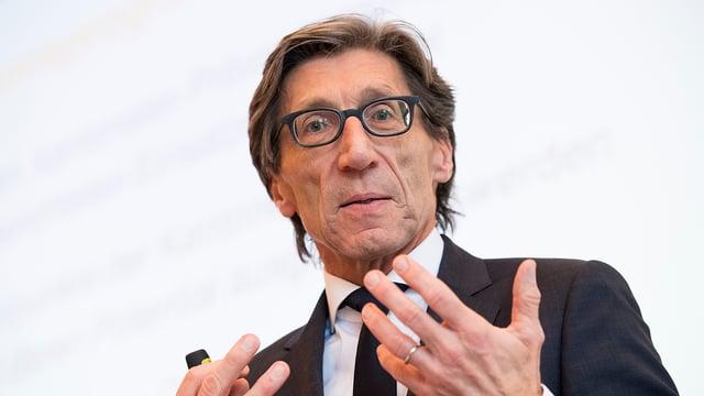 Älterer Mann mit Brille und dunklem Haar und schwarzem Anzug schaut in die Kamera.