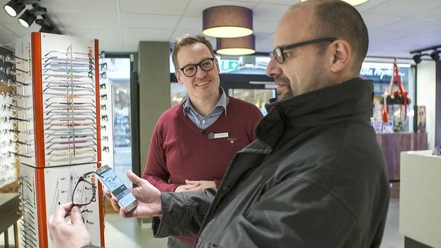 SRF-Redaktor Reto Widmer im Optikergeschäft. Er vergleicht ein Brillenmodell auf der Minden-App mit dem physischen Modell im Geschäft.