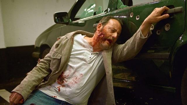 Ein Mann hängt angeschossen an der Tür eines Autos.