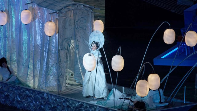 Eine Frau in weissem Gewand auf einem Schiff voller Lampions.