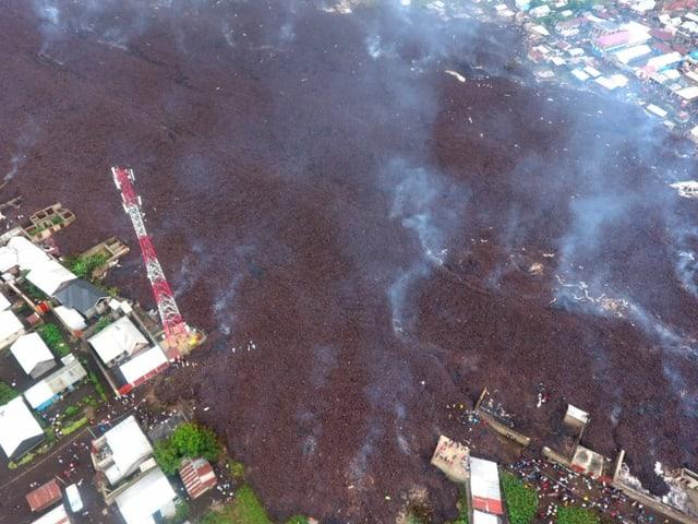 Luftaufnahme des Lavastroms der sich über eine grosse Fläche hinein in Siedlung erstreckt.