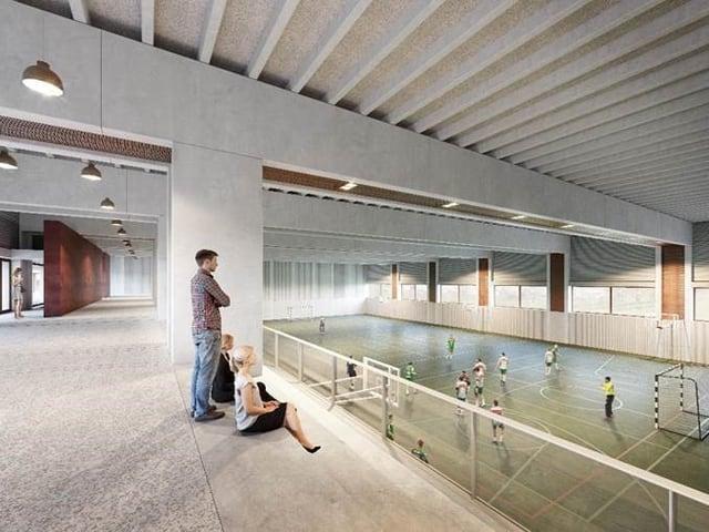 Eine Dreifachsporthalle mit Tribüne.