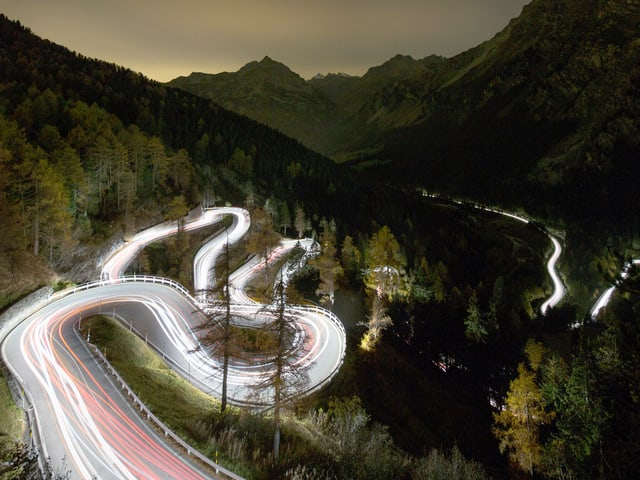 Nachtaufnahme einer kurvigen Strasse in einer Berglandschaft.