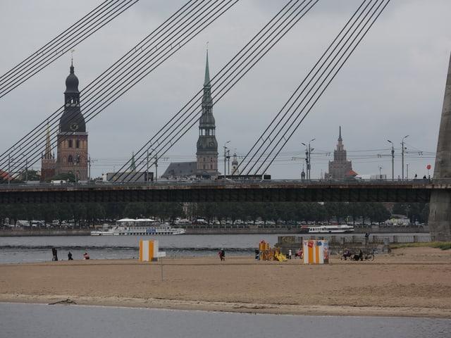 Ansicht der Altstadt von Riga hinter einer modernen Hängebrücke.