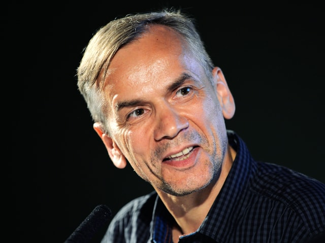 Das Porträt eines Mannes mit kurzen grauen Haaren, der in die Kamera lächelt.