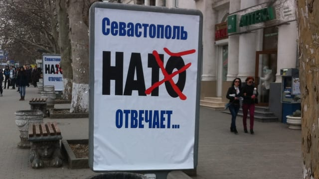 Plakat mit dem durchgekreuzten Schriftzug HATO (Nato)