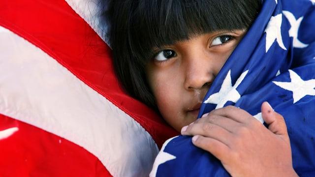 Ein Kind mit hispano-amerikanischem Aussehen schmiegt sich an eine US-Flagge.