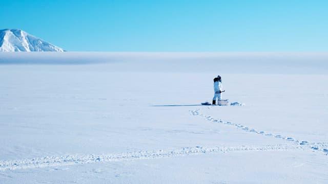 Sebastian Gerland bohrt ein Loch ins Meereis, um dessen Dicke messen zu können.