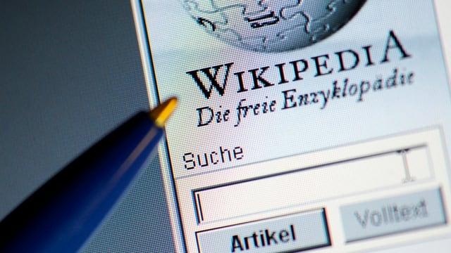 Ein Kugelschreiber zeigt auf einem Computerbildschirm auf die offene Wikipedia-Startseite mit Suchfenster.