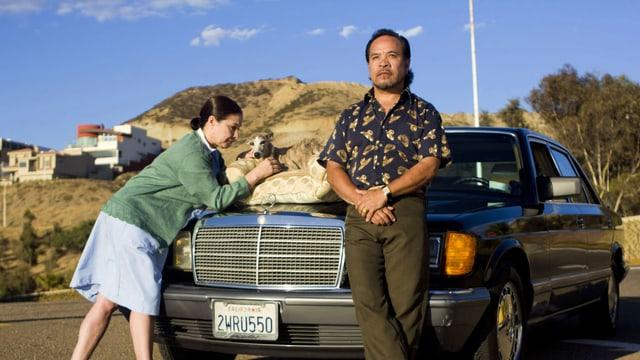 Auf der Kühlerhaube eines parkierten Mercedes sitzt ein Windhund. Er wird gestreichelt von der Hausangestellten Lidia, danbeben steht der Chauffeur und betrachtet den Sonnenuntergang.