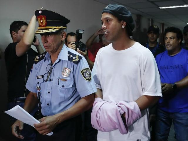 Ronaldinho wird in Asuncion von einem Polizisten aus dem Gericht eskortiert.