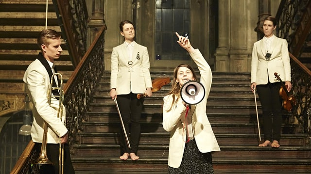 Theaterszene: Drei Musiker schauen auf eine Frau, die gestikulierend in ein Megaphon spricht.