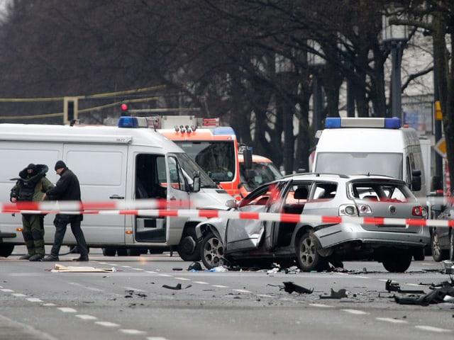 Das zerstörte Auto - im Hintergrund Polizei und Feuerwehr