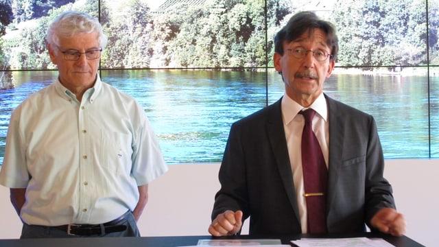 Raphaël Rohner und Caro Stemmler stehen vor einem Bild mit dem Rheinufer.