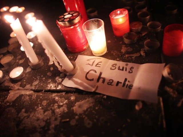 Kerzen und ein Zettel mit der Aufschrift «Je suis Charlie»