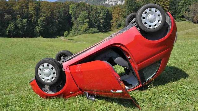 Rotes Auto liegt kopfüber im Gras
