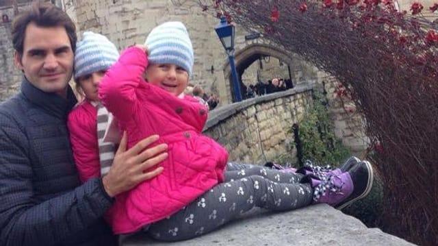 Roger Federer mit den Zwillingsmädchen, die auf einer Mauer sitzen.