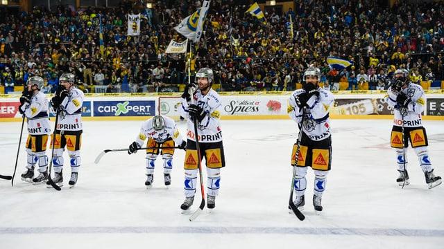 Enttäuschte Eishockey-Spieler stehen auf dem Eis nach einer Niederlage.