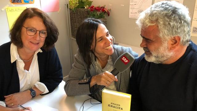 Annette König sitzt neben Khaled Khalifa an einem Tisch und interviewt ihn