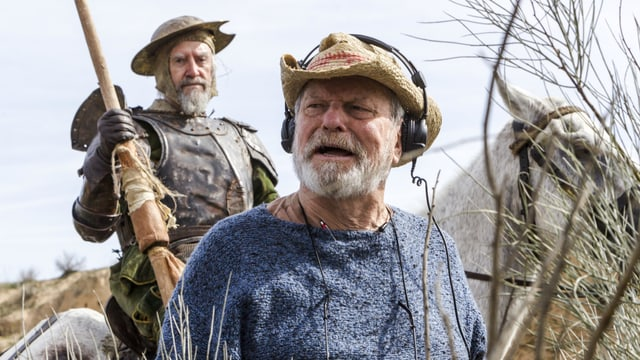 Mann mit Kopfhörern draussen, im Hintergrund EIn Mann in alter Ritterrüstung auf einem Pferd.