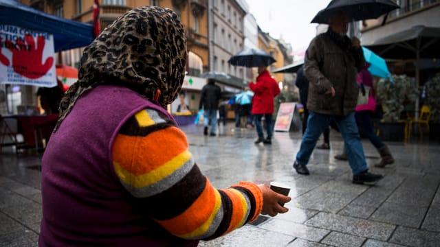 Ältere Frau auf kniend und bettelt um Geld