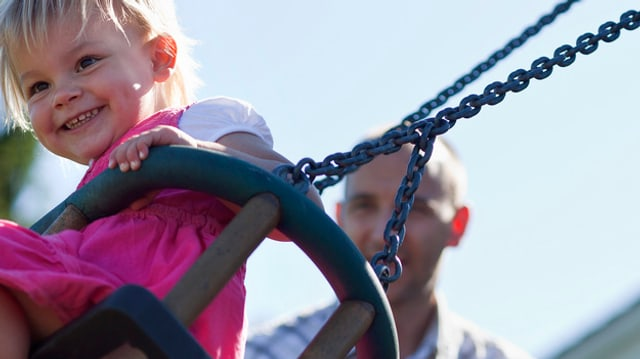Ein Kind auf einer Schaukel - dahinter ein Vater