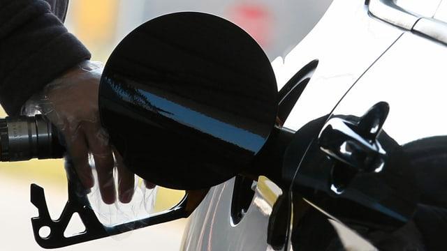 Purtret d'ina persuna che tanca benzin vid in tancadi.