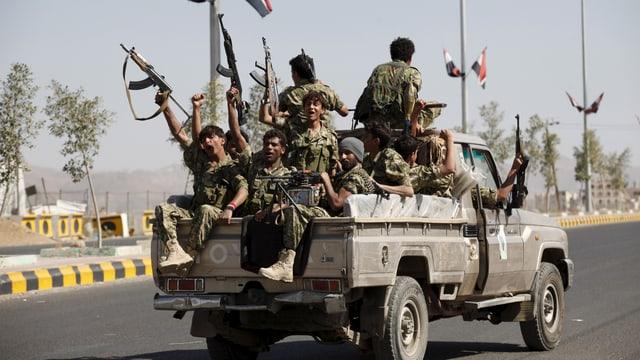 Bewaffnete Kämpfer sitzen auf der Ladefläche eines Pickups.