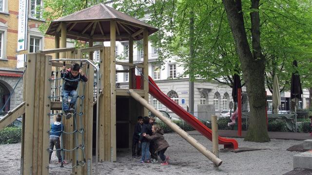 Spielgeräte mit spielenden Kindern im Vögeligärtli in Luzern.