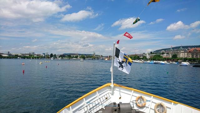 panorama da la bartga cun bandiera grischuna sin la riva dal lai