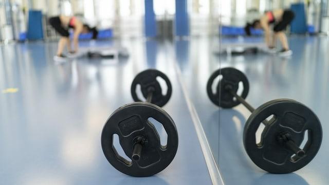 Hanteln im Fitnesszentrum vor Spiegtelwand, Frau dehnt sich.
