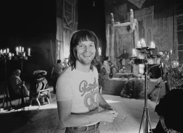 Ein Mann mit halblangen Haaren und einem Print-Shirt in einer Kirche lächelt in die Kamera.
