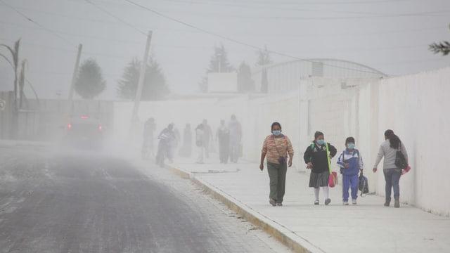 Menschen mit Mundschutz laufen auf der Strasse