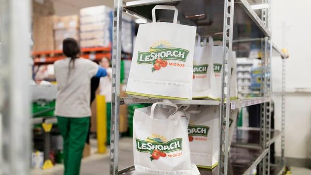 Einkaufstüten mit dem Le-Shop-Logo stehen in einem Regal.
